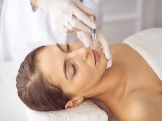 Obraz na płótnie Canvas Beautician doing beauty procedure with syringe to face of young brunette woman. Cosmetic medicine and surgery, beauty injections