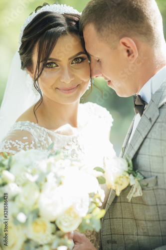 Photo couple in wedding attire with a bouquet of flowers and greenery is in the hands