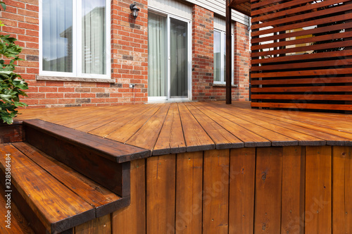 Fototapeta Backyard wooden deck floor boards with fresh brown stain obraz