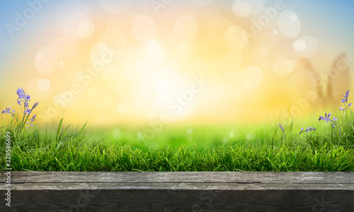 Fototapeta A wooden table top product display with a fresh sunny Easter background of blue sky and  warm bokeh with green grass meadow foreground. obraz