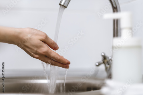 Fotografía Woman washes hands on a white background