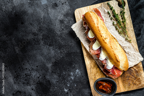 baguette sandwich with jamon ham serrano, paleta iberica, Camembert cheese on the cutting Board Canvas Print