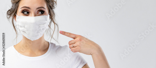 Cuadros en Lienzo Beautiful caucasian young woman in white t-shirt with disposable face mask