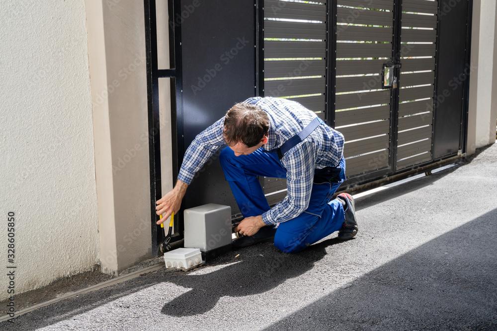 Fototapeta Repairman Fixing Broken Automatic Door