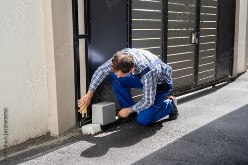 Fotografie, Obraz Repairman Fixing Broken Automatic Door