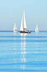 Sloop rigged yachts sailing in a Mediterranean sea on a clear sunny day, Spain. Blue sky with white clouds, reflections on water