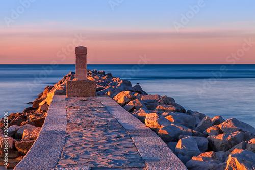 Alba sul mare con obelisco e rocce Canvas Print
