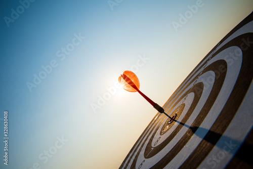 Fotomural Close up shot red darts arrows in the target center on dark blue sky background