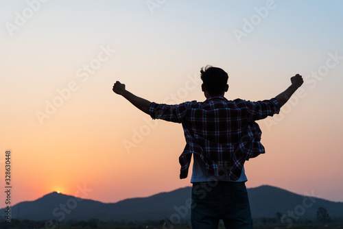 Cuadros en Lienzo Man with fist in the air during sunset sunrise mountain in background