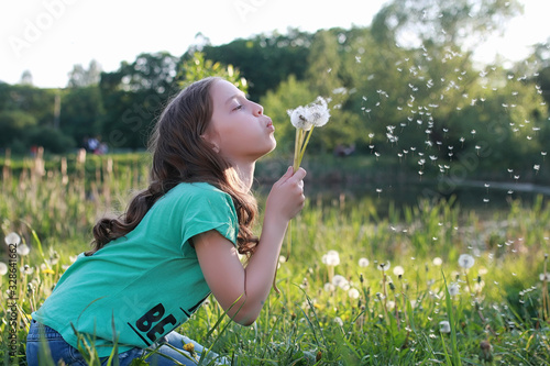 Canvas-taulu Teen blowing seeds from a dandelion flower in a spring park