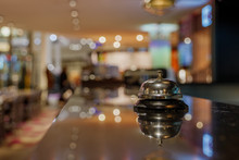 Selected Focus View At Ring Bell For Call Service On Counter   At Bar In Front Of Desk Kitchen With Blur Background Of Restaurant's Atmosphere.