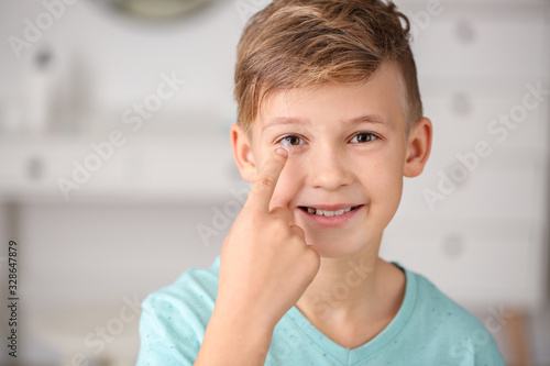 Fotomural Little boy putting in contact lens at home