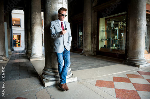 Well dressed man using his mobile phone leaning against a column on the classic Canvas-taulu