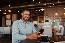 Cheerful Handsome African Young Man Relaxing In Modern Cafe Using Mobile Phone While Drinking Coffee