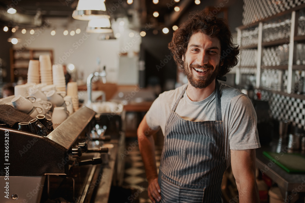 Fototapeta Portrait of handsome young male coffee shop owner standing behind counter