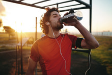 Close-up Portrait Of A Caucasian Young Man With Earphones In His Ears Drinking Water After Exercising In The Outdoor Gym Park