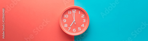 Red clock alarm clock on colored background divided vertically into red and green color web banner: planning or working time concept