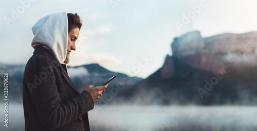 Carta da parati hipster tourist using smartphone planning trip on foggy lake, mist in mountain n