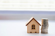 Financial growth concept, real estate tax. Miniature house and a stack of coins. Financial growth concept, real estate tax, buying and selling houses, insurance. Miniature house and a stack of coins.