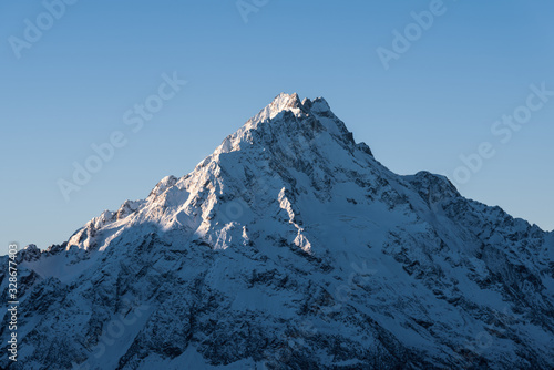 Photo The top of a snowy mountain early in the morning at dawn