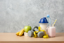 Protein Cocktail, Dumbbells, Measuring Tape, Water Bottle And Fresh Fruits On Wooden Table