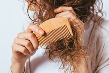 Young Woman Combing Tangled Ends Of Her Curly Hair