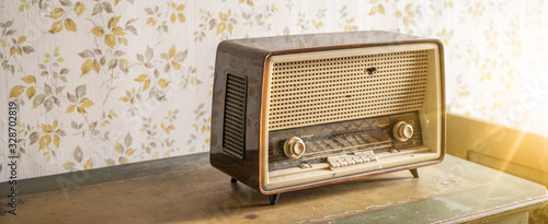Fotografia Old retro vintage radio on a aged wooden table illuminated by the sun