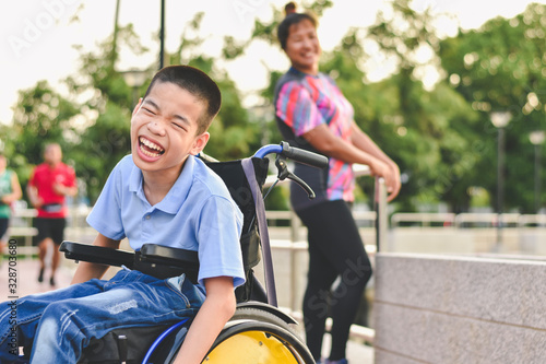 Obraz Disabled child on wheelchair is play and learn in the outdoor park like other people, Life in the education age of special children, Happy disability kid concept. - fototapety do salonu