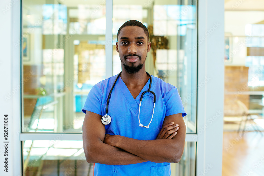 Fototapeta Portrait of a serious young male doctor or nurse wearing blue scrubs uniform and stethoscope, with arms crossed in hospital
