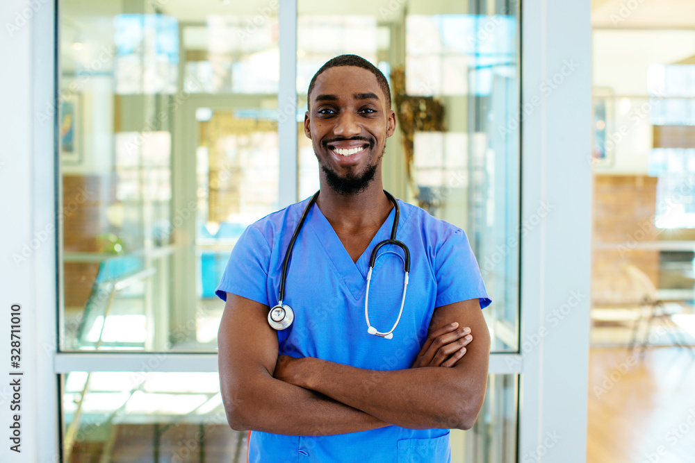 Fototapeta Portrait of a friendly male doctor or nurse wearing blue scrubs uniform and stethoscope, with arms crossed in hospital
