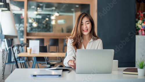 Fototapeta Charming asian businesswoman sitting working on laptop in office. obraz