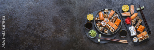 Fototapeta sushi rolls with rice and fish, soy sauce on a dark stone background obraz