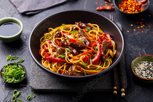 Photo Stir fry noodles with vegetables and beef in black bowl