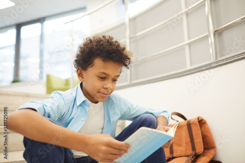 Obraz Horizontal medium portrait of curious African American boy reading interesting book sitting alone on stairs, copy space - fototapety do salonu