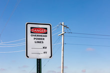 Road Sign Warning Of Overhead Power Lines Danger. Electrical Transmission Wires And Pole In Background