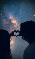 Couple making heart shape under the starry skies.