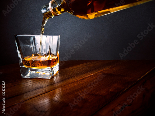 Pouring whisky into glass on wooden table - serve whiskey Fototapeta
