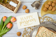Jewish Holiday Passover Greeting Card With Matzo, Seder Plate, Wine And Tulip Flowers On Wooden Table.