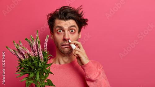 Sick young man has allergic reaction to flowering plant, uses nasal spray to cure rhinitis, has red swelling eyes, symptoms of allergy, unhealthy look, sneezes all time Wallpaper Mural