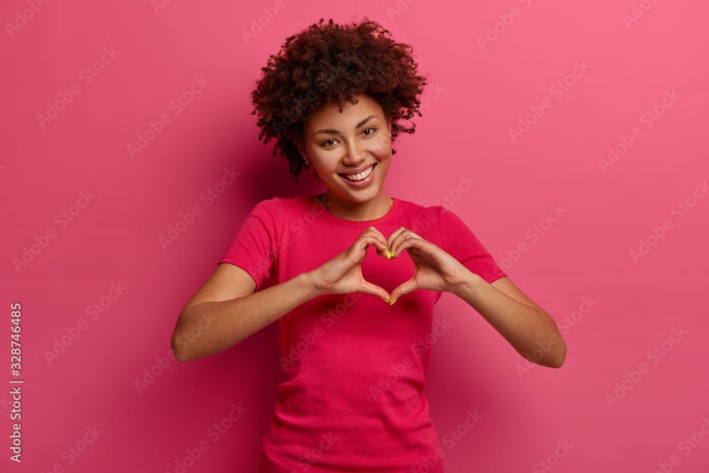 Fototapeta Pretty curly African American woman confesses in love, makes heart gesture, shows her true feelings, has happy expression, wears casual red t shirt, poses over pink background. Relationship concept