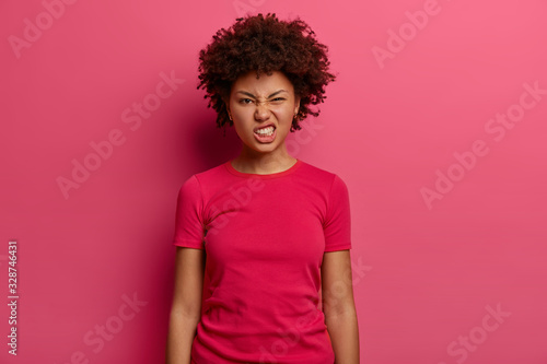 Leinwand Poster Annoyed dissatisfied woman clenches teeth and feels irritated, looks in displeasure at camera, dressed in casual t shirt, poses indoor against pink background