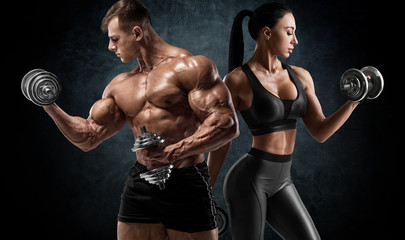 Fototapeta na wymiar Sporty couple workout with dumbbells. Muscular man and woman showing muscles