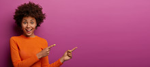 Happy Reaction On Advert. Positive Excited Woman Has Afro Hairstyle, Dressed In Orange Jumper, Has Widely Opened Eyes, Shows Blank Space On Purple Background For Your Promotion Or Information