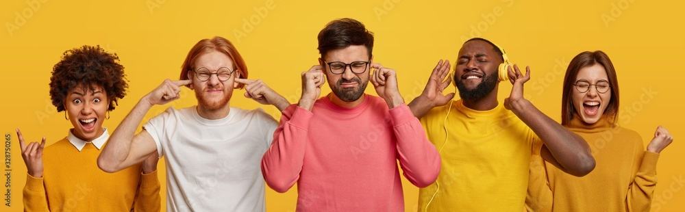Fototapeta Group of millennial women and men spend free time on party, listen loud music, plug ears to avoid loud sound, make rock n roll gesture and fist bump, isolated over yellow background, feel happy