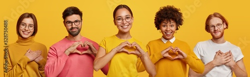 Photo Horizontal shot of happy women and men show heart gesture, express love, say be my valentine, keep hands on chest, feel thankful, isolated on yellow background, confess in truthful feelings
