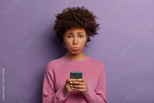 Unhappy disappointed woman with Afro hair, purses lower lip, holds smartphone, s Tablou Canvas