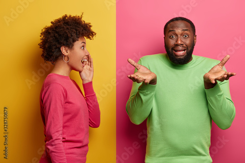 Photo Disappointed black man spreads palms, looks hesitant and unhappy, faces problematic situation, positive Afro American woman whispers secret to boyfriend, stands sideways