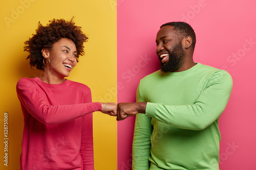 Positive dark skinned young woman and man bump fists, agree to be one team, look Canvas