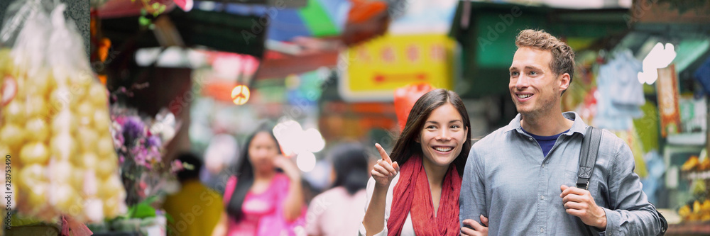 Fototapeta China food market travel people tourists shopping in alley street in Hong Kong. Asian woman Caucasian man couple traveling in Asia, chinese city lifestyle. Banner panorama.