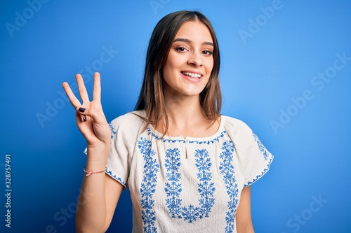 Obraz na plátne Young beautiful brunette woman wearing casual t-shirt standing over blue background showing and pointing up with fingers number three while smiling confident and happy